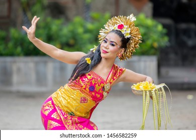 Picture of Balinese dancer dancing Pendet dances with a bowl of flower petals at outdoor