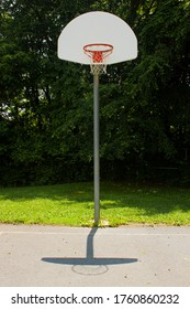 Picture of a basketball post with hoop, breakaway rim, backboard and net.  Image is taken in the concrete basketball field of an elementary school at midday.