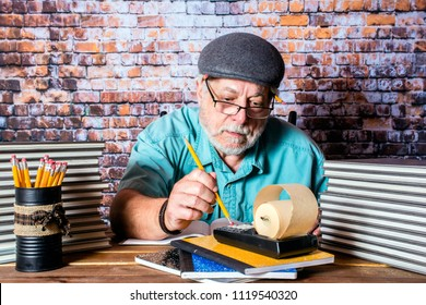 picture of bearded elderly male accountant doing the books with pencil and old adding machine with stacks of books and can full of pencils
