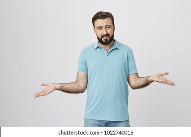 Picture of bearded handsome man looking questioned standing with spread hands over white background. Middle aged guy do not know what everyone want from him so he lifts his arms and askes straight.