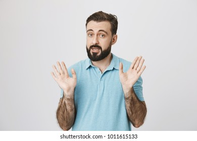 Picture of bearded man raising his eyebrows high, holding his palms up near white wall. Emotions and gesture concept. Person tells his employer that it was not him who stole all pensils from office.