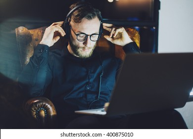 Picture bearded man wearing glasses relaxing modern loft office.Banker sitting vintage chair,listening music laptop night.Using contemporary notebook,blurred background.Horizontal,film effect