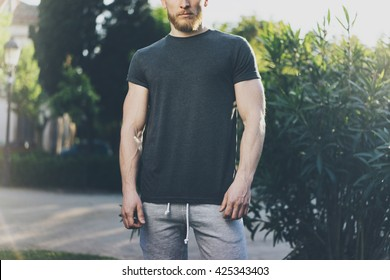 Picture Bearded Muscular Man Wearing Black Empty t-shirt and shorts in summer holiday. Green City Garden Park Background. Front view. Horizontal Mockup