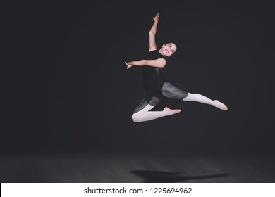 Picture of beautiful ballerina looks happy while performing dances in dark background