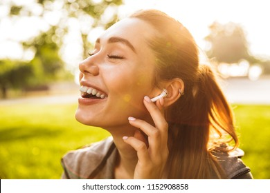 Picture of beautiful cute fitness sports woman in park outdoors listening music with earphones.