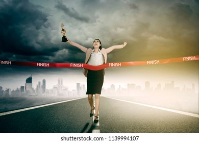 Picture of beautiful entrepreneur carrying a trophy while crossing the finish line. Shot on the road