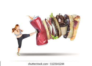 Picture of beautiful fat woman wearing sportswear while kicking soft drink and fast food, isolated on white background