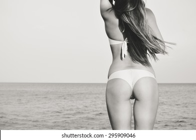 Picture of beautiful girl perfect butt over open water on sunny outdoors copy space background, black and white photography