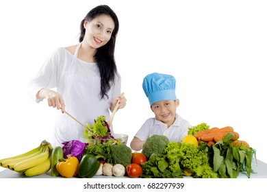 Picture of a beautiful mother and her son smiling at the camera while making a healthy salad, isolated on white background