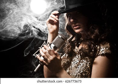 Picture of beautiful singer in dress with studio microphone
