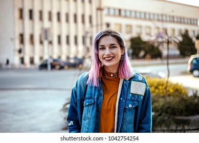 Picture of beautiful smiling rebellious woman with dyed hair at city street.