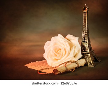 Picture of beautiful still life, old paper scroll with white rose on the table and little Eiffel tower souvenir, dark grunge background, retro style photo, love letter, romantic poem, Valentines day