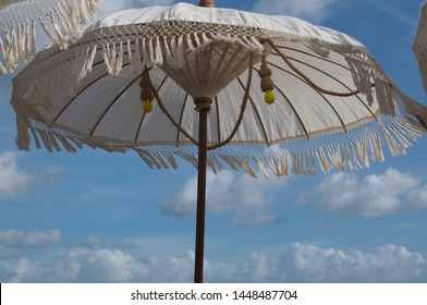 Picture of a beautiful white Balinese sun umbrella, decorated with yellow bulb lights and located at the famous Echo Beach in Canggu, Bali - Indonesia