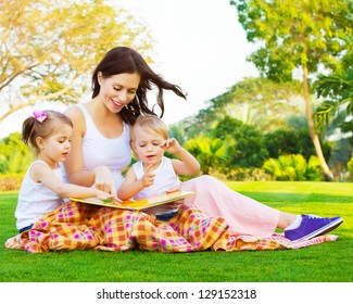 Picture of beautiful woman with daughter and son sitting down on green grass field and read fairytale, cute female with two little children enjoying book outdoors, preschool education, happy family