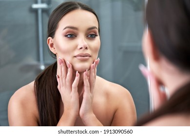 Picture of beautiful woman looking on reflection in the mirror after shower