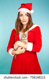 Picture of beautiful woman in new year costume holding a kitten on blue background