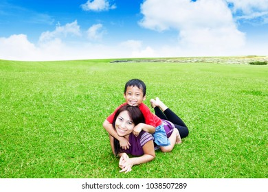 Picture of beautiful woman playing with her son while lying in the park