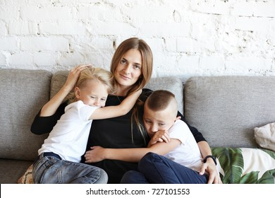 Picture of beautiful young Caucasian mother smiling happily, embracing her children: little boy with short haircut having sad mournful look as he doesn't gain love and attention from his busy mother