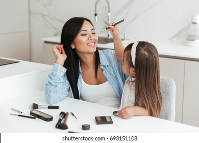 Picture of beautiful young woman with little daughter at home indoors doing makeup.