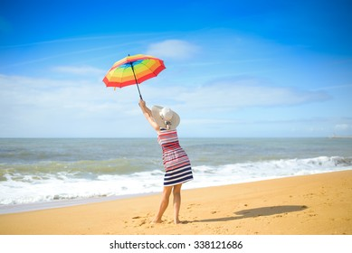 Picture of beautiful young woman with rainbow umbrella standing on seashore. Backview of pretty lady in hat on blurred summer sky outdoor background.