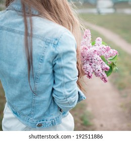 Picture from behind girl in a denim jacket and lilac flowers in their hands