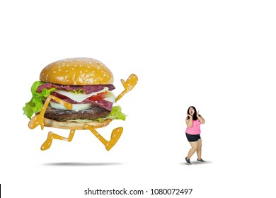 Picture of big hamburger chasing fat woman while running in the studio, isolated on white background