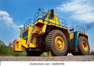 A picture of a big yellow mining truck at work site on blue sky with white clouds background