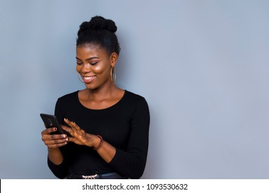 picture of a black african girl on black long sleeves smiling while using her phone