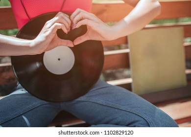 A picture of black vynil leaning to girl's body. She is sitting on bench and crossing her legs. Girl is shwoing the love sign with her fingers in front of vynil disk.