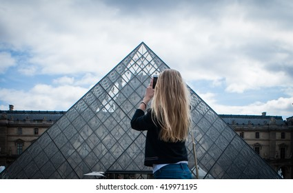 Picture of a blond girl taking a picture of the Louvre