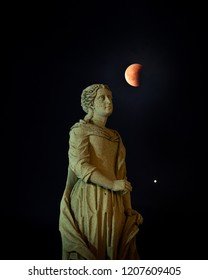 Picture of the blood Moon eclipse emerging from behind the statue of a Saint with Mars below it.