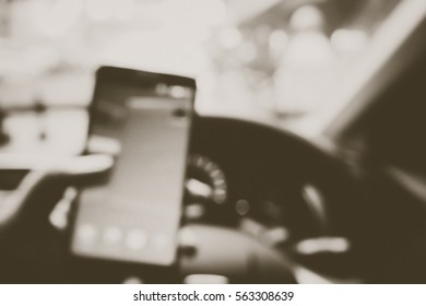 Picture blurred  for background abstract and can be illustration to article of Hand using a smartphone while driving a car