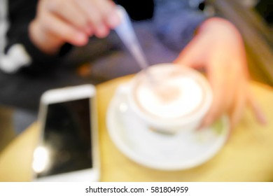 Picture blurred  for background abstract and can be illustration to article of woman with coffee and smartphone