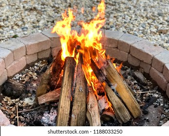 Picture of a bonfire, burning firewood brightly, in a brick firepit on a summer evening/night.
