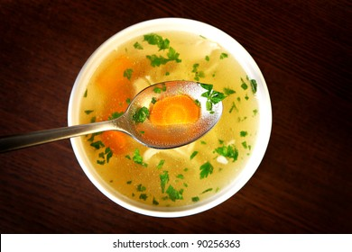 A picture of a bowl of traditional chicken soup served in a bowl over wooden background