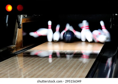 Picture of  bowling ball hitting pins scoring a strike