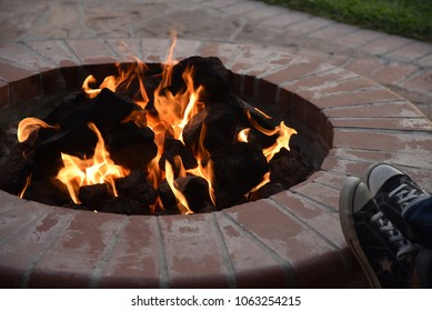 A picture of a brick backyard fire pit with someone resting their feet on the edge