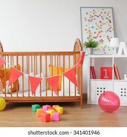 Picture of bright newborn room interior with colorful toys