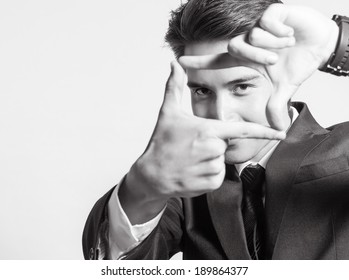 Picture of business man creating frame with fingers.