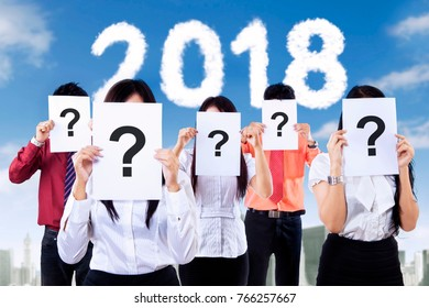 Picture of business people covering their face with question mark in the paper. New Year 2018 concept