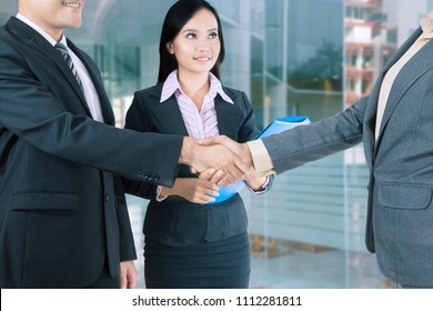Picture of business people shaking hands after doing negotiation while standing in the office