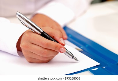 Picture of a business woman hand signing the contract