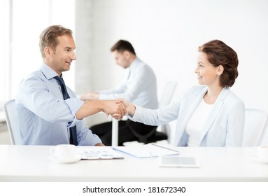 picture of businessman and businesswoman shaking hands in office