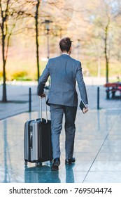 picture of a businessman who walks with a trolley bag in the city