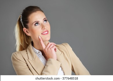Picture of businesswoman thinking over grey background