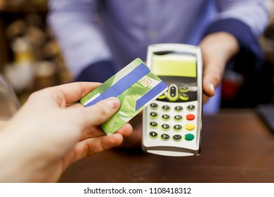 Picture of buyer with bank card and seller with terminal in hand