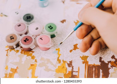 Picture by numbers. Drawing on canvas. Male hand with brush. Numbered paint cans. Creative hobby. Painting for beginners. Novice artist. Art idea.Brushes and paints