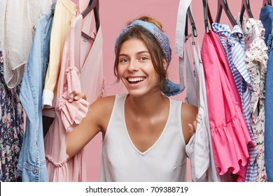 Picture of casually dressed young woman with joyful smile feeling happy after she rearranged, reorganized and refreshed her wardrobe, got rid of old clothes. Clothing, fashion and style concept