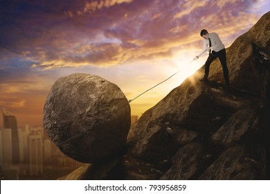 Picture of Caucasian businessman pulling a rock while climbing a cliff. Shot at sunrise time