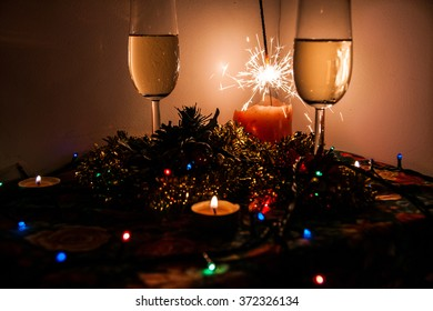 Picture of champagne glasses on Christmas lit up by candles. light garlands and sparklers